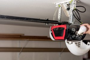 A garage door opener owner changing its LED lightbulb. Similar in style to the Liftmaster WLED, a battery backup garage door opener.