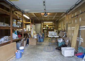 A messy garage with an open garage door. Cleaning out the garage is the perfect Spring activity.