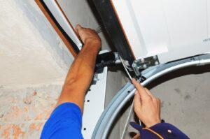 What happens when the garage door is noisy? You fix it! An Environmental Door technician repairs a loose garage door panel.