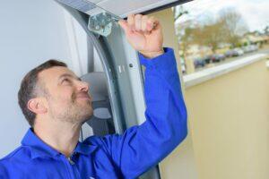 A technician checking the panels of a garage door to improve the garage door lifespan.