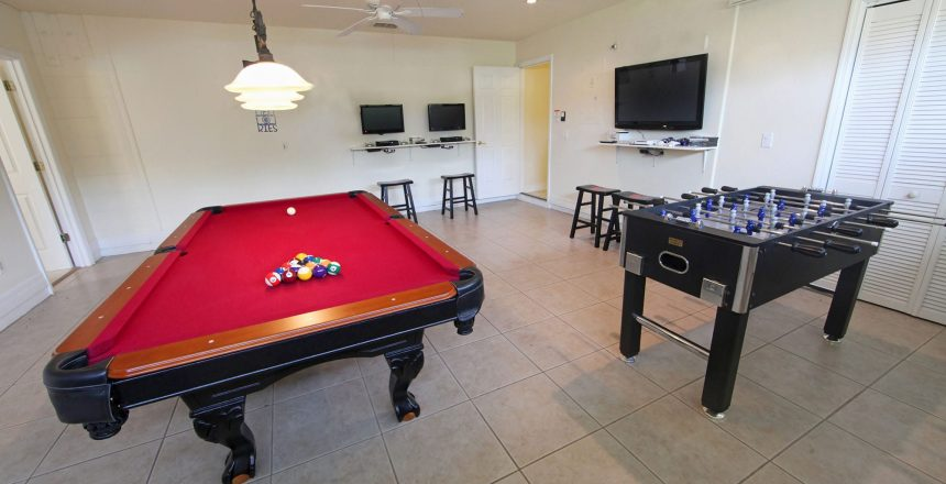 Converting a garage into an enteratinment space is nothing new, but you still have need protection. A pool table and foosball table in a converted garage.