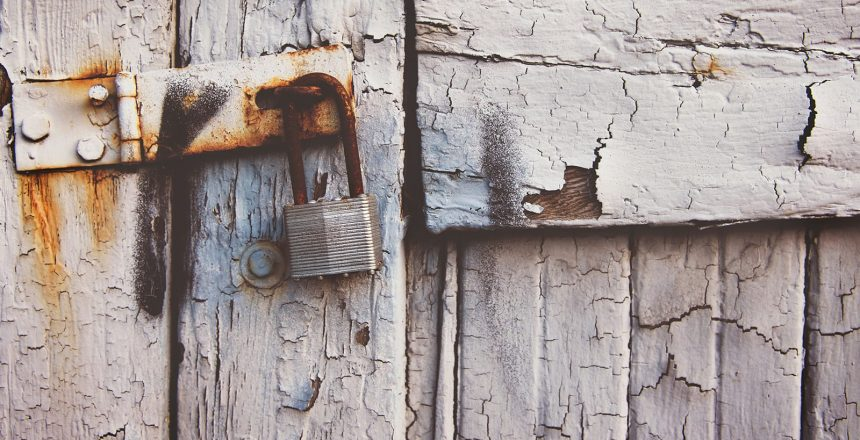 Proper garage door security means more than a lock. A rusted lock on a dilapidated garage door.